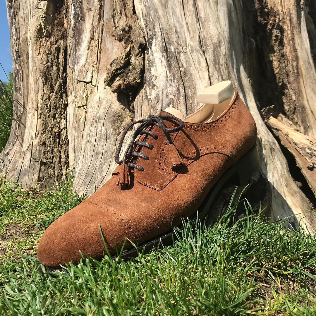 bespoke brown shoe with lace tassels on a tree stump